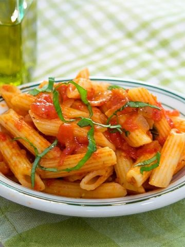 Pasta d'Arrabiata is a delicious combination of pasta, bacon and fiery red pepper flakes with wonderful fresh basil. Top with Parmesan for serving. From @NevrEnoughThyme https://www.lanascooking.com/pasta-darrabiata/