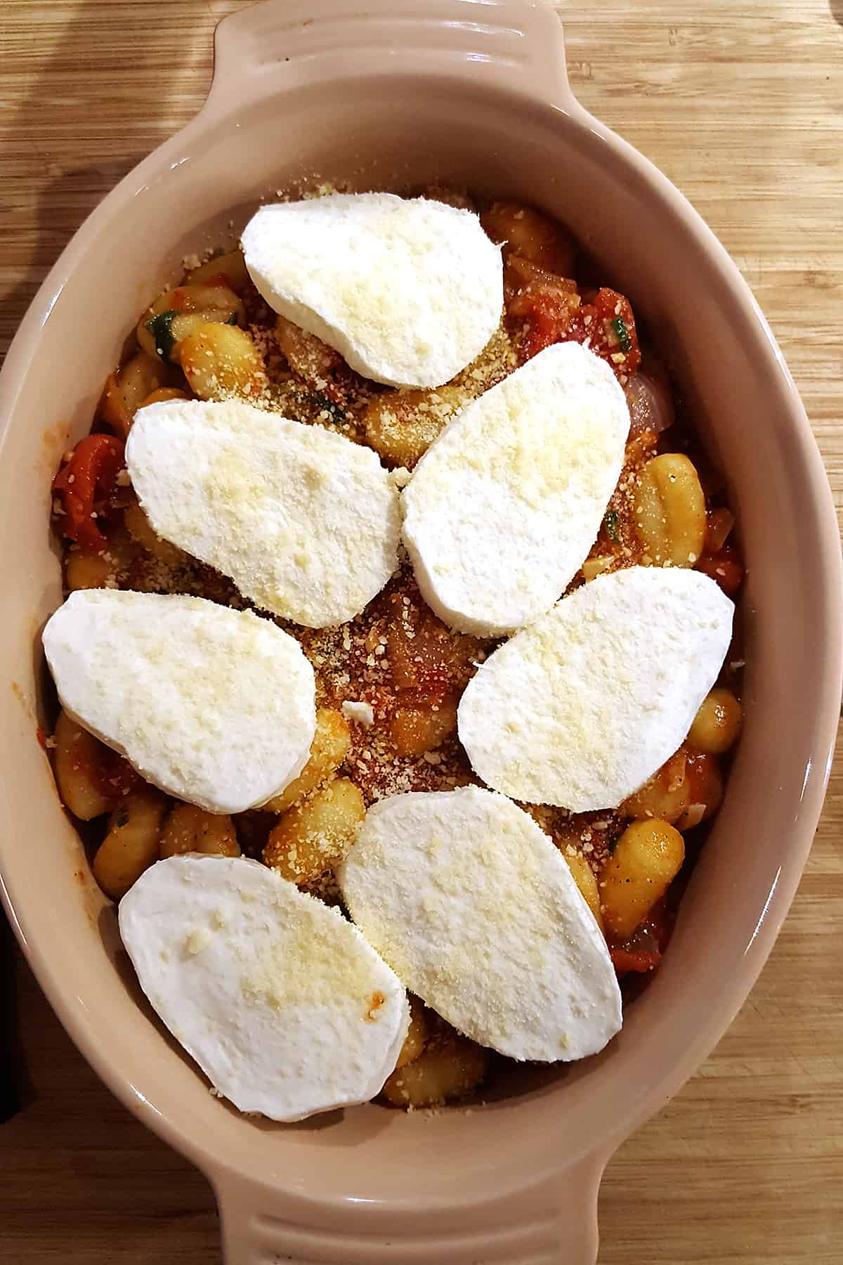 Gnocchi and tomato sauce topped with mozzarella and Parmesan cheeses.