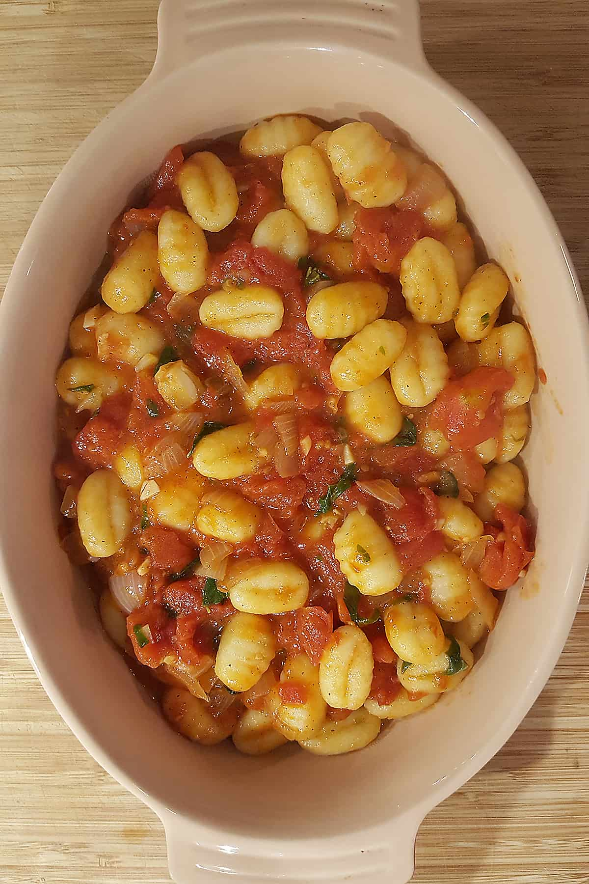 Gnocchi and tomato sauce in baking dish.