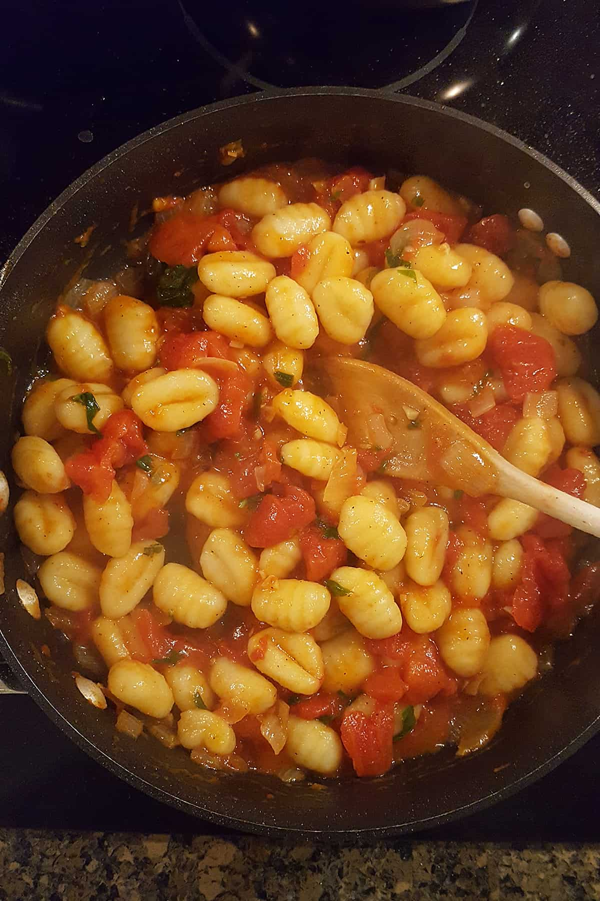 Gnocchi mixed with tomato sauce.
