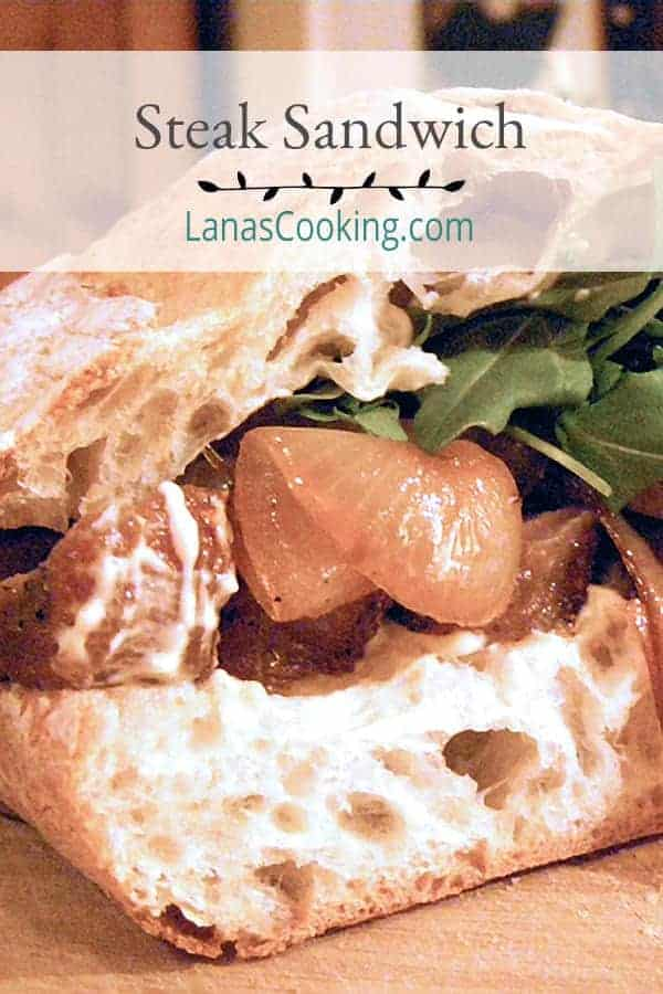 A luscious Steak Sandwich piled high with grilled onions, a spicy mustard mayo, and arugula on ciabatta bread. A meal all on its own. From @NevrEnoughThyme https://www.lanascooking.com/steak-sandwich/