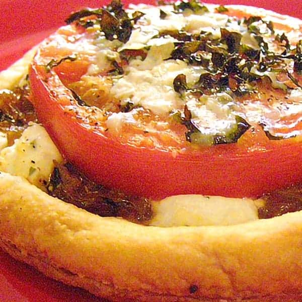 Savory Tomato Goat Cheese Tarts made with purchased puff pastry, fresh tomatoes, goat cheese, and fresh basil. Lovely to serve for a spring brunch. From @NevrEnoughThyme https://www.lanascooking.com/savory-tomato-goat-cheese-tarts/
