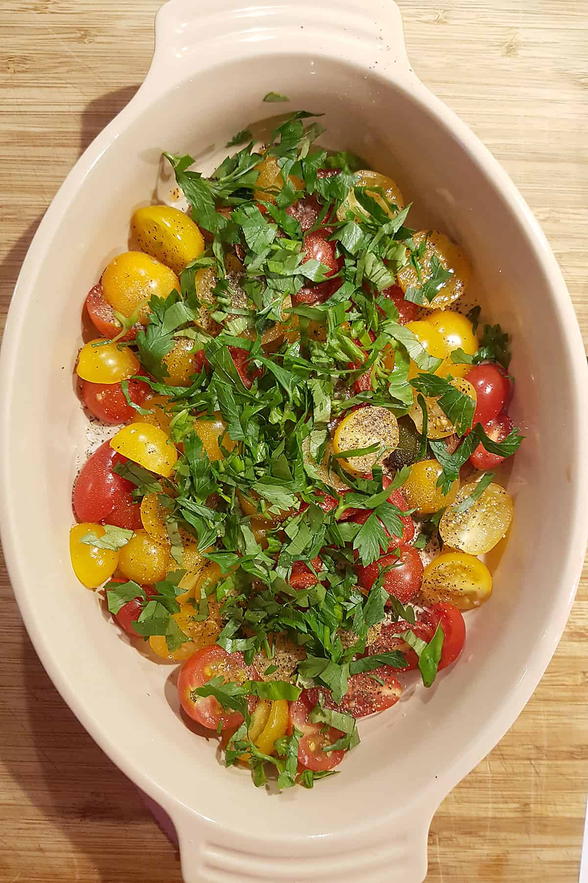 Ovenproof baking dish with halved cherry tomatoes and herbs