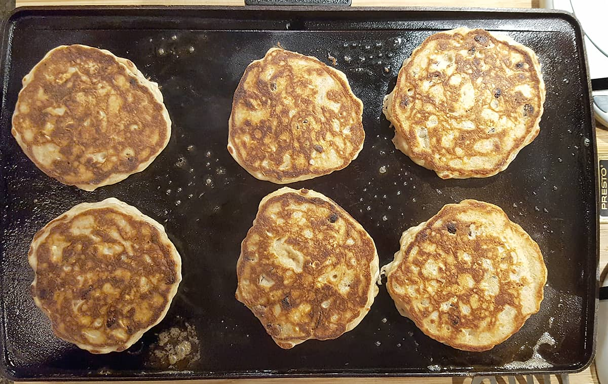 Griddle showing golden brown second side of pancakes