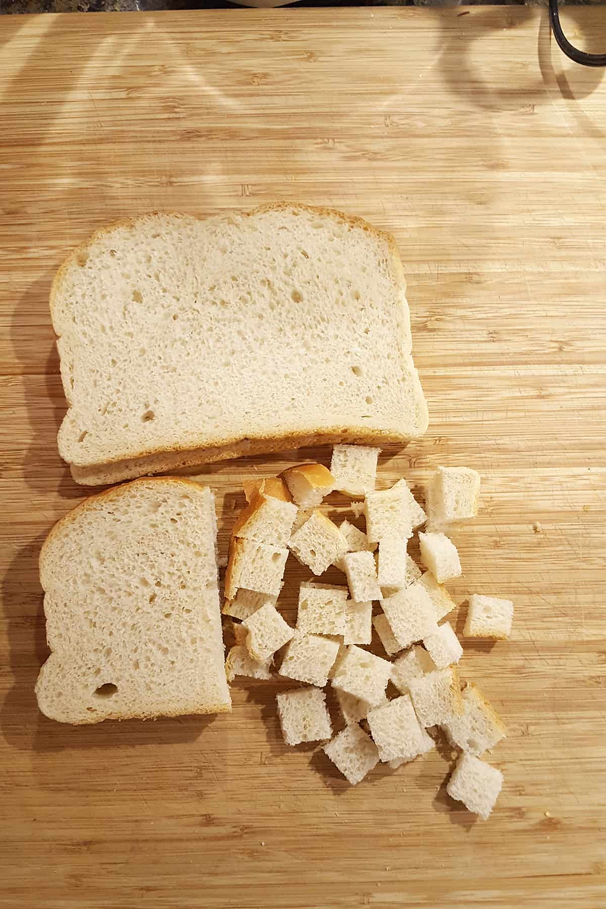 Bread slices cut into ½ inch cubes on a cutting board