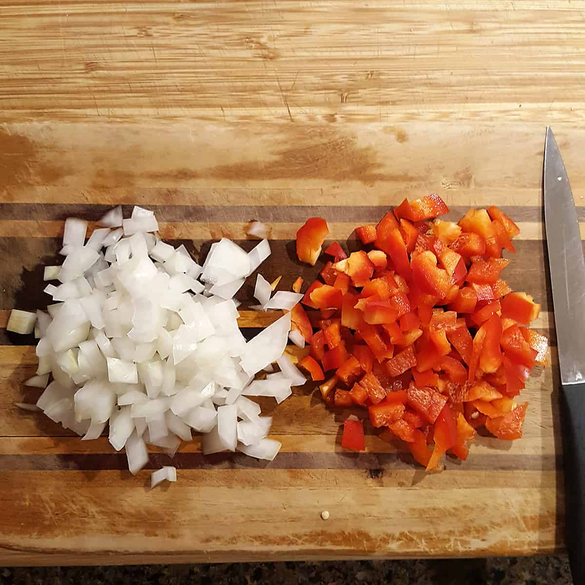 Diced onions and peppers on a cutting board