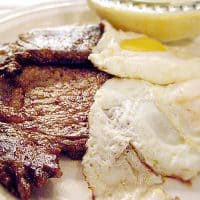 Serve steak and eggs for a hearty weekend breakfast - thin cut, seasoned steaks grilled and served with over easy eggs and a side of cheese grits. From @NevrEnoughThyme https://www.lanascooking.com/steak-and-eggs/