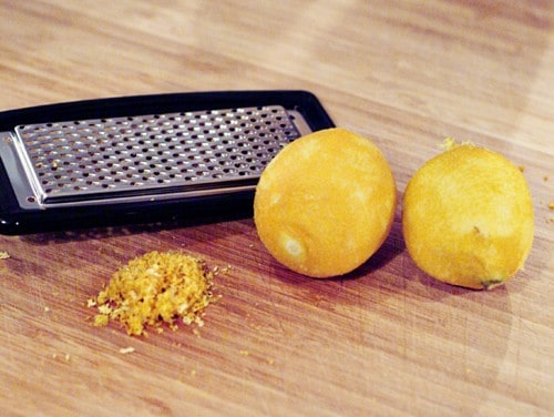 Two lemons and a zester on a cutting board.