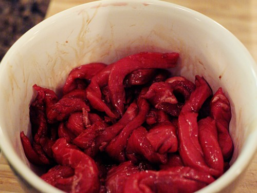 Beef strips marinating in a bowl.