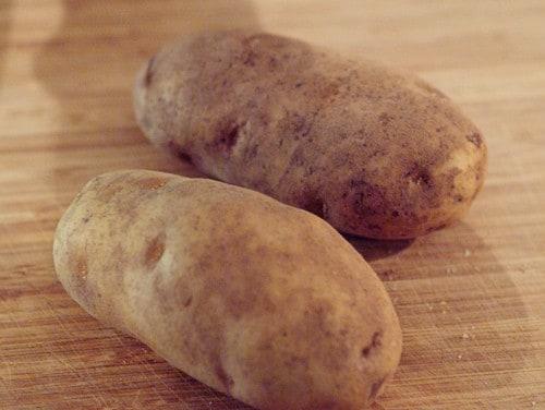 Two baking potatoes on a board