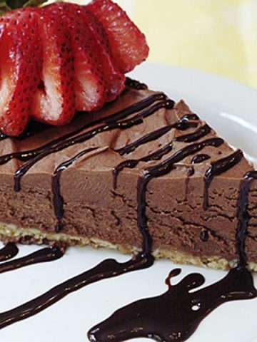 A simple and delicious, No Bake Chocolate Cheesecake with an almond and cookie base filled with chocolate, cream cheese, and whipped cream. From @NevrEnoughThyme https://www.lanascooking.com/no-bake-chocolate-cheesecake/