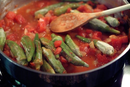 Adding okra to cooked onions and tomatoes in a skillet.