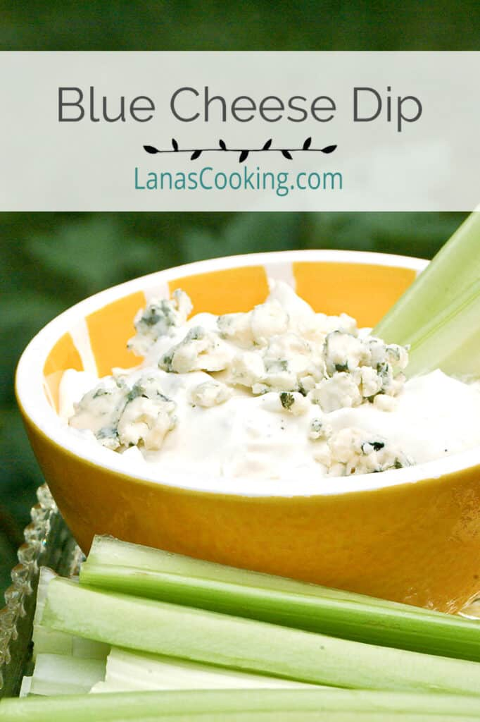 Blue cheese dip in a decorative bowl with celery sticks alongside.