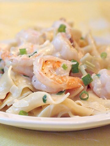 Creamy shrimp and pasta - succulent shrimp in a creamy Parmesan sauce served over egg noodles. From @NevrEnoughThyme https://www.lanascooking.com/creamy-shrimp-and-pasta/