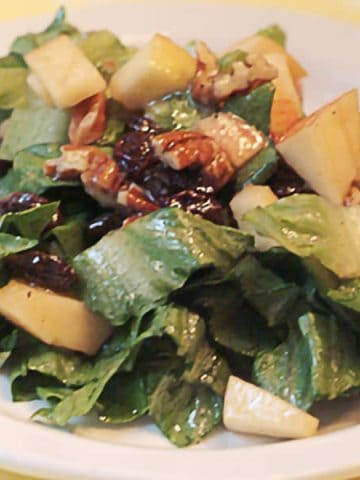 This Mixed Green Salad with Apples Raisins and Pecans contains all the elements of the classic Waldorf Salad dressed with a red wine vinaigrette. From @NevrEnoughThyme https://www.lanascooking.com/fruited-green-salad/