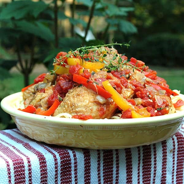Chicken Cacciatore with tomatoes, peppers, and onions slowly stewed and served over pasta. An Italian favorite for family dinners. From @NevrEnoughThyme https://www.lanascooking.com/chicken-cacciatore/