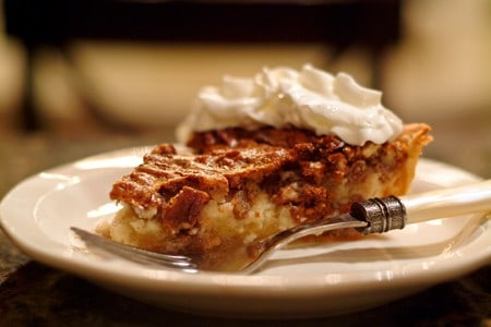 Pecan Cheesecake Pie slice topped with whipped cream