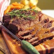 Pot roast sliced and presented on a serving board with gravy over top.