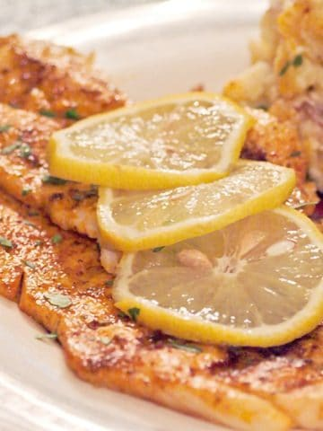 Grilled fish with lemon slices presented on a white plate.