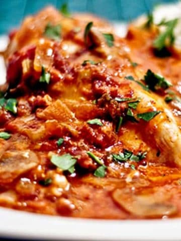 Bistro Chicken is chicken simmered in a tomato and mushroom sauce topped with cheese and bacon. Serve with mashed potatoes for a great weeknight dinner. From @NevrEnoughThyme https://www.lanascooking.com/bistro-chicken/