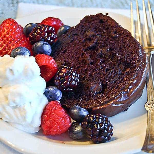 Berry Glazed Chocolate Cake - a moist devil's food cake topped with a raspberry glaze and chocolate icing. Perfect for any celebration. From @NevrEnoughThyme https://www.lanascooking.com/berry-glazed-chocolate-cake/