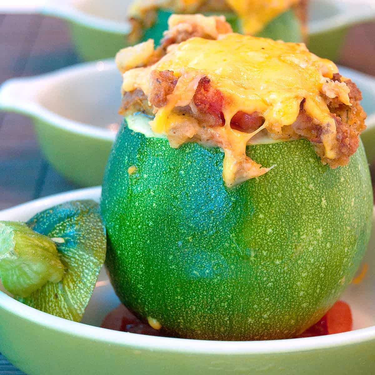Baked stuffed 8-Ball Zucchini in a green serving dish.