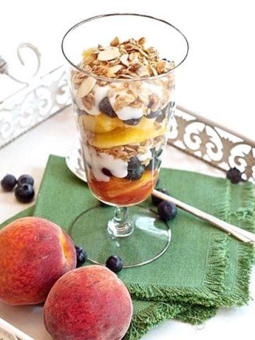 Peach Blueberry Yogurt Parfait. A summery yogurt parfait - layered ripe, juicy sweet peaches, blueberries and vanilla yogurt topped with lowfat granola. From @NevrEnoughThyme https://www.lanascooking.com/peach-blueberry-yogurt-parfait/