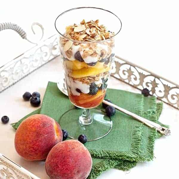 Peach-Blueberry Yogurt Parfait. A summery yogurt parfait - layered ripe, juicy sweet peaches, blueberries and vanilla yogurt topped with lowfat granola. From @NevrEnoughThyme http://www.lanascooking.com/peach-blueberry-yogurt-parfait/