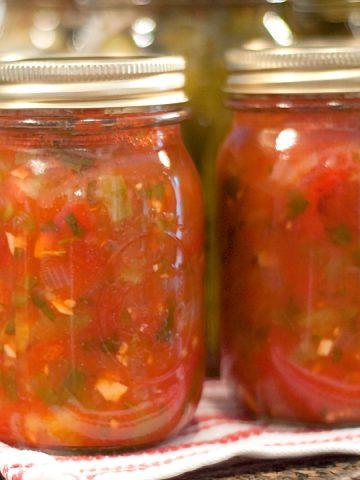 Jars of finished basic salsa lined up on a kitchen towel.