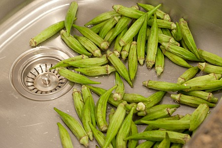 Okra being washed in the kitchen sink.