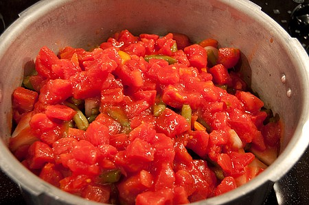 Add tomatoes into the pressure cooker on top of the veggies.