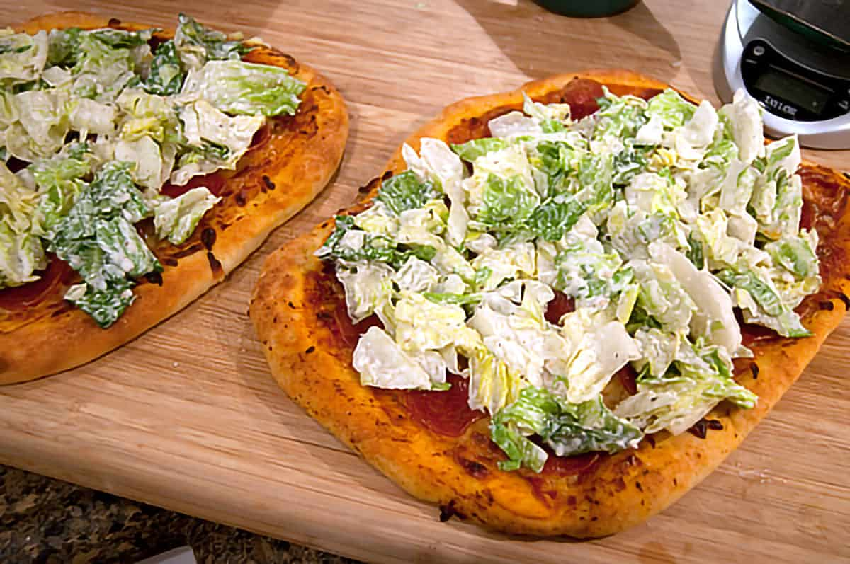 Baked pepperoni pizzas topped with Caesar salad.