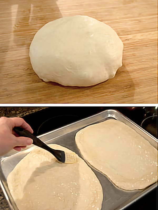 Pizza crust dough divided in half and placed on a baking sheet. Being brush with olive oil.