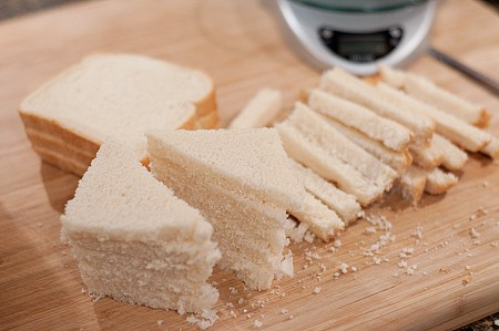Slices of bread with crusts removed on a cutting board.