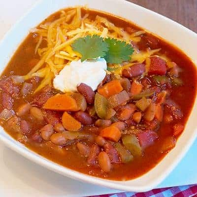 Vegetable Chili - this recipe for meatless vegetable chili is hearty, spicy and full of beans and veggies. Make it truly vegetarian with a vegetable stock. From @NevrEnoughThyme https://www.lanascooking.com/vegetable-chili/