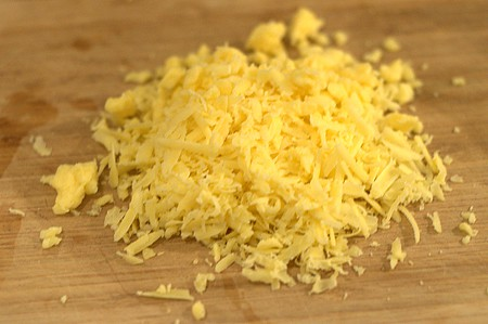 Grated sharp cheddar cheese on a cutting board.