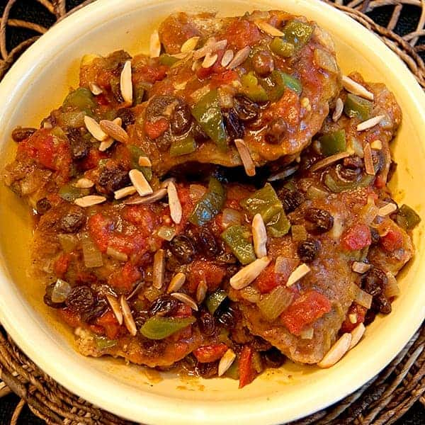 Chicken Country Captain is a true old South classic. Chicken, onions, garlic, peppers and curry powder with raisins and toasted almonds. From @NevrEnoughThyme https://www.lanascooking.com/chicken-country-captain/