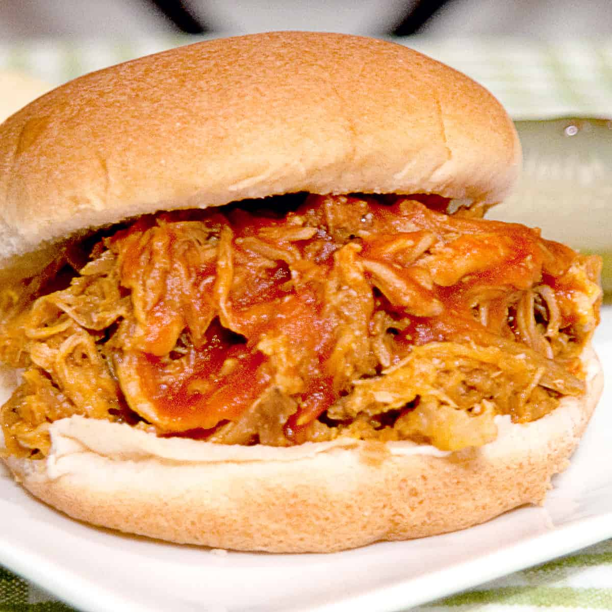 Pulled pork barbecue sandwich on a white serving plate.
