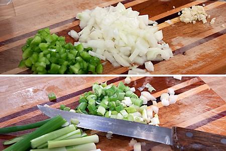 Diced onion, green pepper, garlic, and scallions on a cutting board.