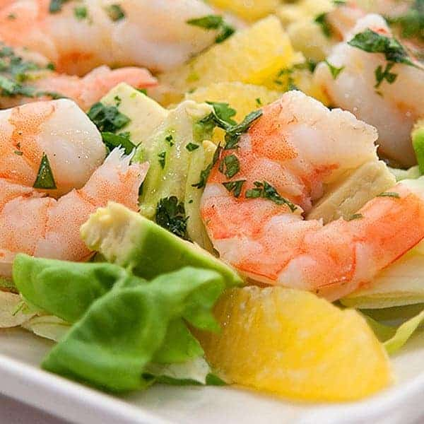 This winter shrimp salad recipe contains shrimp, avocado and orange sections on a bed of butter lettuce topped with a tangy citrus dressing. From @NevrEnoughThyme https://www.lanascooking.com/winter-shrimp-salad