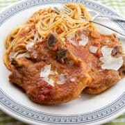 Delicious pork chops simmered in marinara sauce and served over pasta. Great family meal! https://www.lanascooking.com/pork-chops-and-pasta/