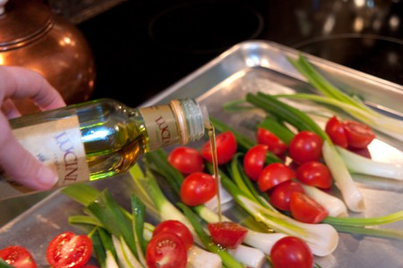 Drizzling olive oil over the vegetables on the baking sheet.