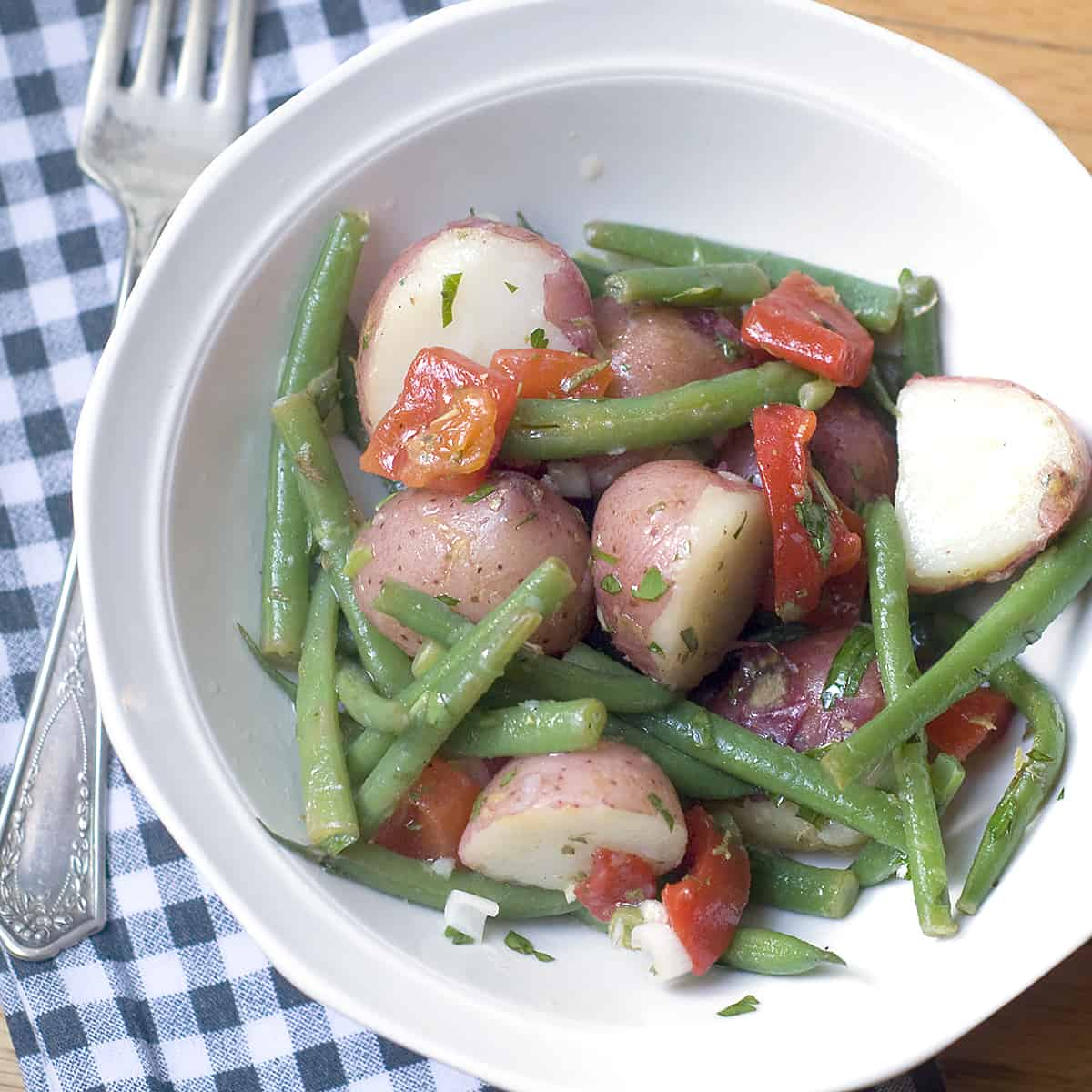 A delicious Warm Vegetable Salad with red skinned potatoes and green beans tossed in a tangy lemon-garlic dressing. Great year round side dish! From @NevrEnoughThyme https://www.lanascooking.com/warm-vegetable-salad/