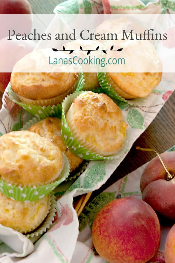 A basket full of peaches and cream muffins with fresh peaches in the foreground.