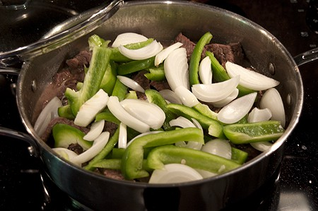 Sliced onions and green bell peppers added to the skillet.