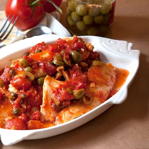 Tilapia Veracruz - tilapia cooked in a flavorful Mediterranean sauce with tomatoes, olives, and capers. From @NevrEnoughThyme https://www.lanascooking.com/tilapia-with-tomato-olive-caper-sauce/
