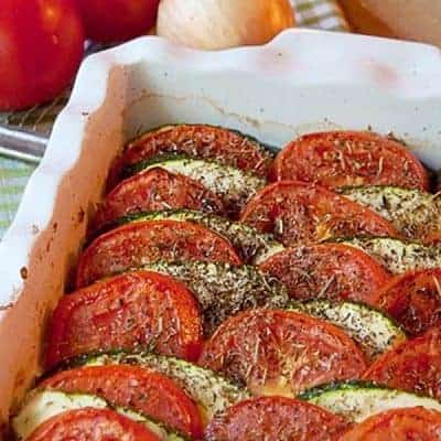 A tian with layers of fresh tomatoes and zucchini over an eggplant and onion base scented with herbes de provence. From @NevrEnoughThyme https://www.lanascooking.com/tomato-zucchini-tian/