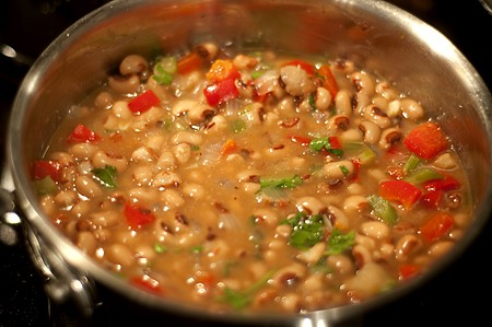 Adding blackeyed peas to vegetables in a skillet.