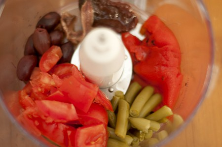 Food processor bowl containing olives, tomatoes, red bell peppers, anchovy, and green beans