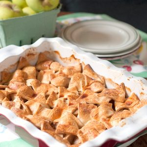 Apple Patchwork Cobbler in a baking dish with serving plates in the background.